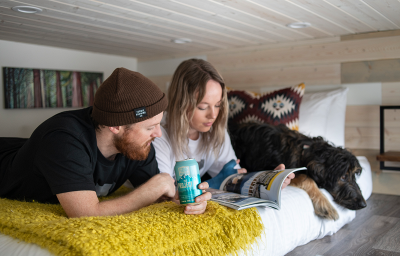 A couple laying on their bed with their dog drinking a beer and reading a magazine
