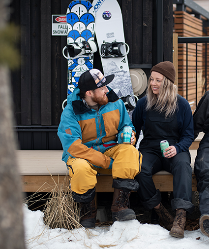 A man and women sat on a deck infront of two snowboards in the snow drinking beers