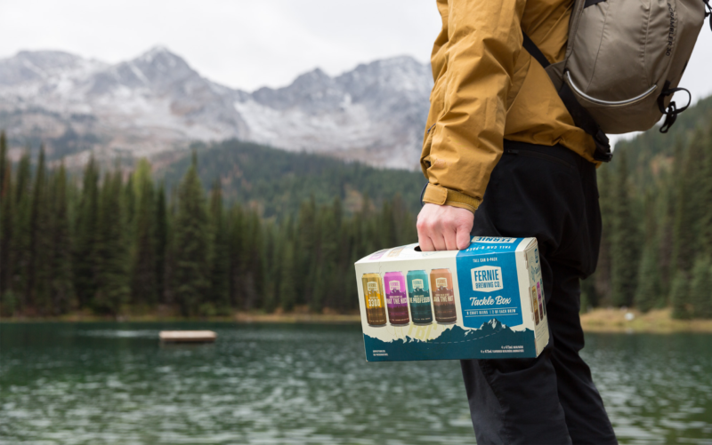 Man stands at a lake at the bottom of a mountain holding a Tackle Box 8-pack mixer