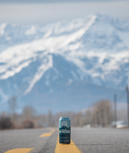 A can of The Professor Amber Lager in the middle of the highway with Fernie Alpine Resort in the background