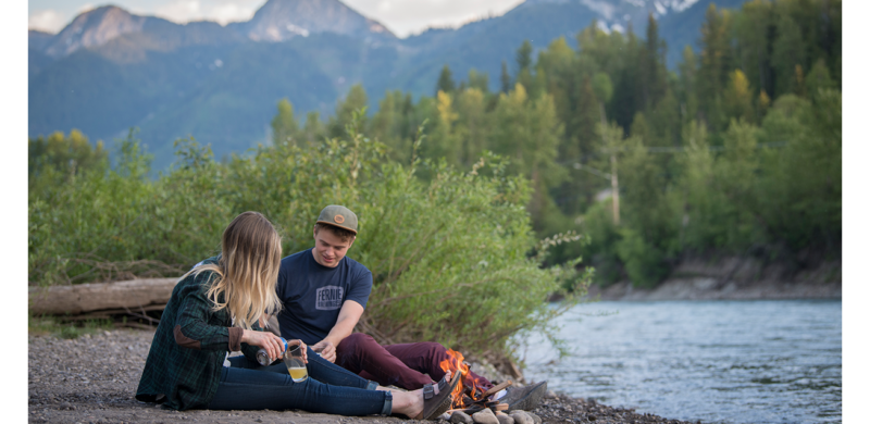 Man and woman sharing a beer by the river with a small fire and mountains in the background