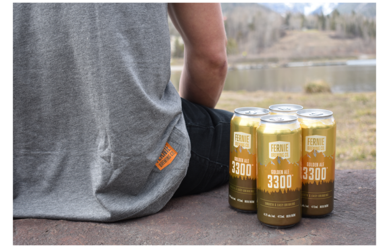 Man sat on a rock with 3300 Golden Ale 4-pack to his right