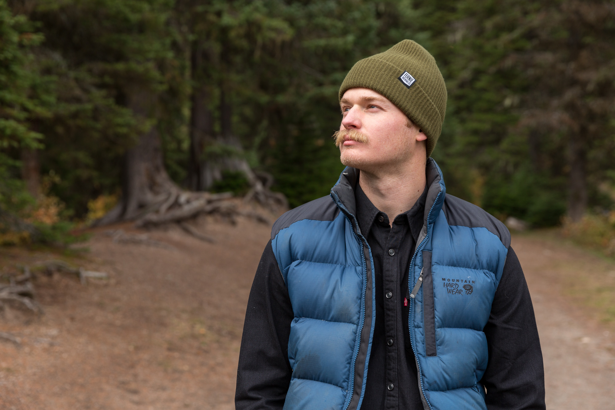 Man in blue vest wearing green toque looking into the distance in the forest.