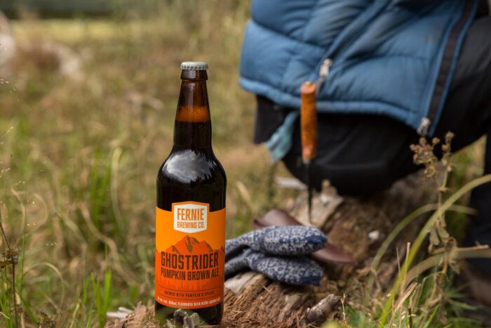 Ghostrider Pumpkin Brown Ale on a log next to mittens