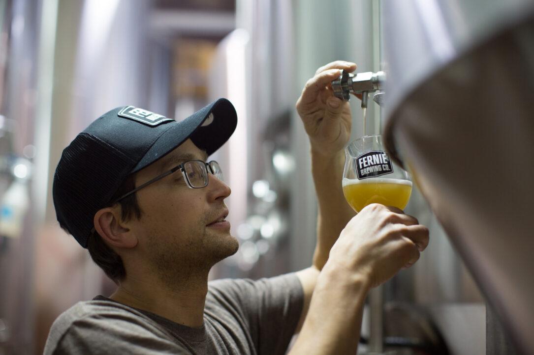 Brewer taking beer sample
