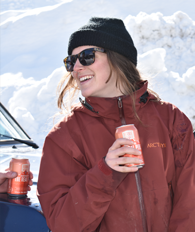 Woman in a ski jacket and black sunglasses and black toque holding a can of The Real Peel Grapefruit IPA