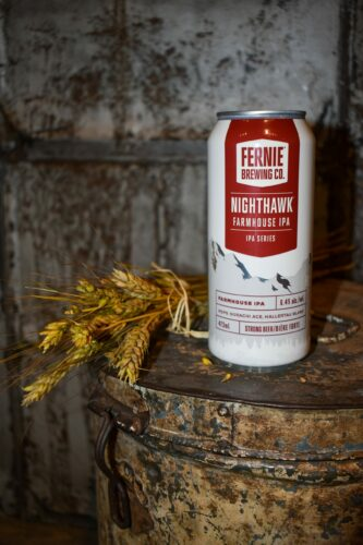 Can of Nighthawk Farmhouse IPA on metal bin next to strands of wheat