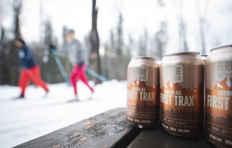 Cross country skiers behind a 6-pack of First Trax Brown Ale