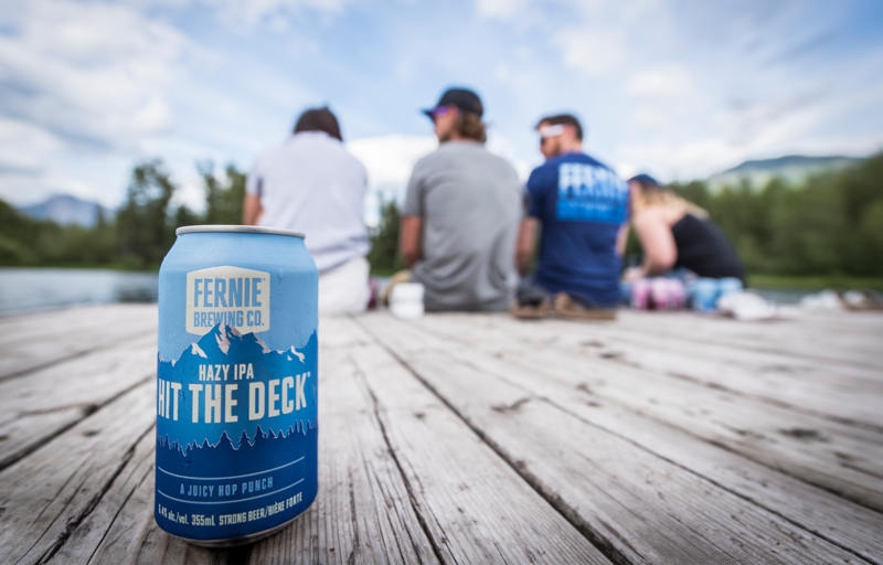 Hit the Deck Hazy IPA in front of people sat on a dock