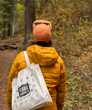 Woman walking through a forest in fall in a yellow puffy coat and an orange cap