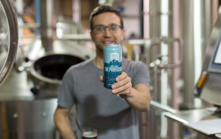 Head brewer Jeff Demaniuk holds up a can of The Professor Amber Lager named after his late father