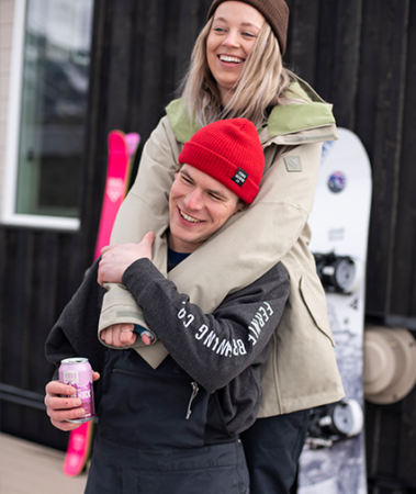 Women with arms around man on a deck in winter with snowboards in the background