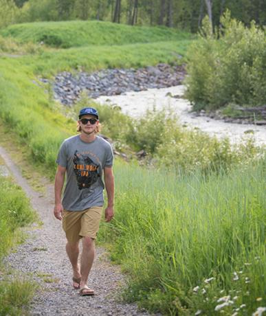Man walking beside a river in summertime Fernie BC