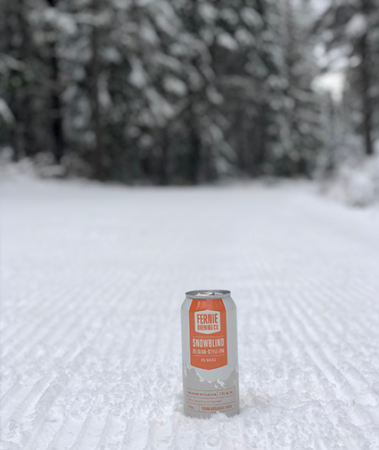 A can of Snowblind Belgian-Style IPA on a groomed cross country skiing trail