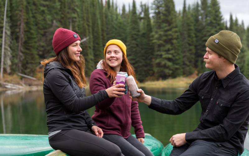 Two women and a man share beers at the side of a lake in Fernie BC