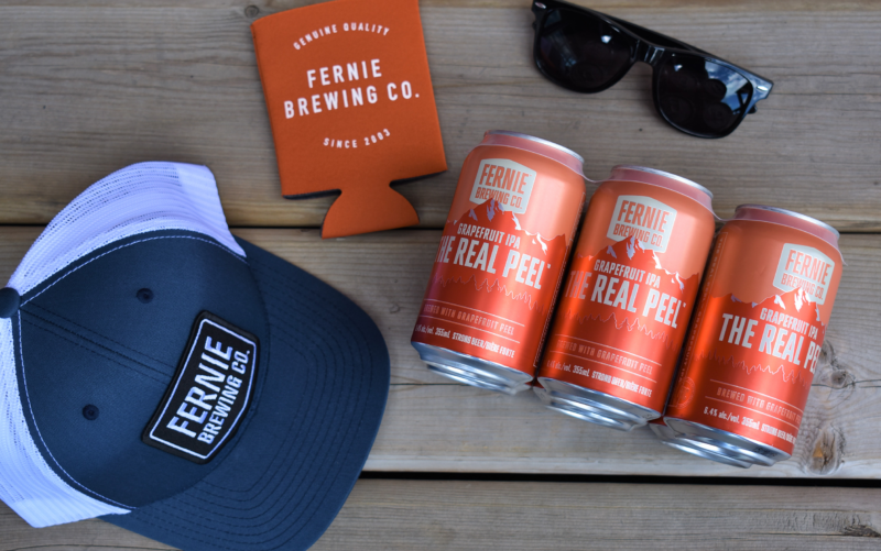 A Fernie Brewing Co. navy blue trucker hat an orange koozie some black sunglasses and a 6-pack of The Real Peel Grapefruit IPA laid out on a deck