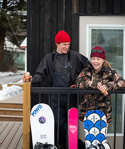 Man and women on a deck with skies and snowboards