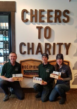 Angel Flight East Kootenay team with Cheers to Charity board at Fernie Brewing Co.