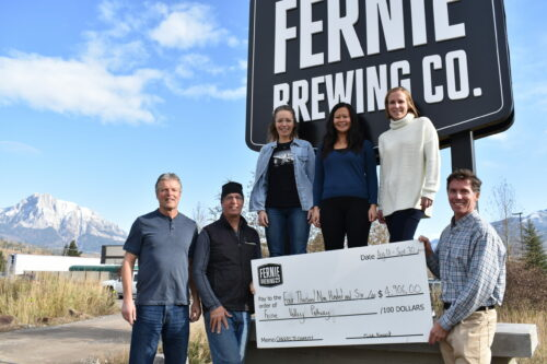 Members of the Fernie Valley Pathway Project recieving a cheque outside Fernie Brewing Co.