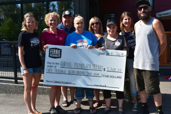 Members of Fernie Friends for Friends receiving a cheque outside Fernie Brewing Co.
