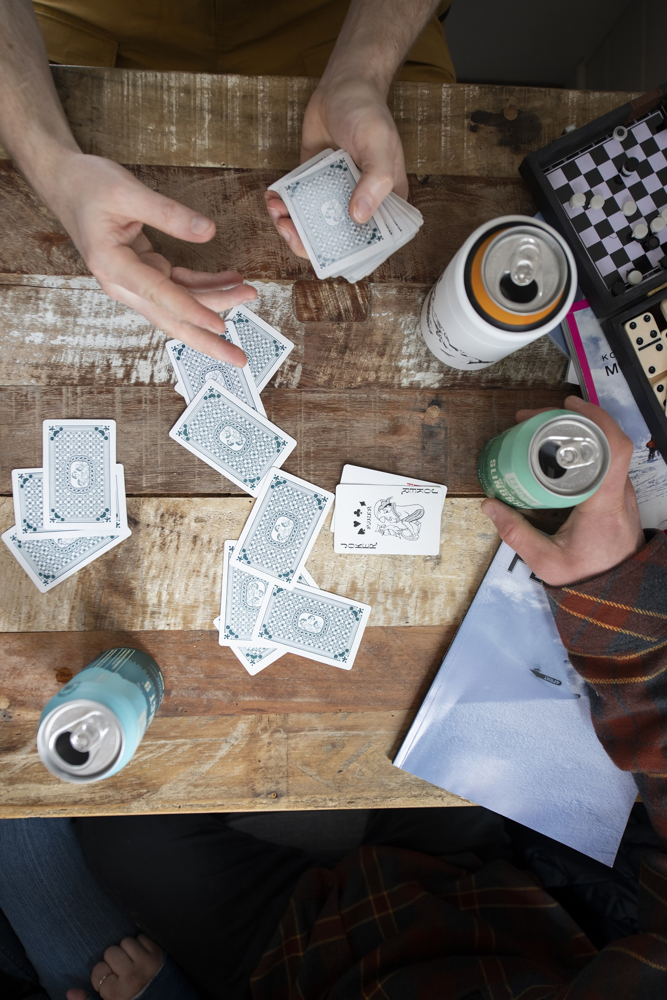 View from above of playing cards being dealt on a wooden table with three Fernie Brewing Co. beers on it.