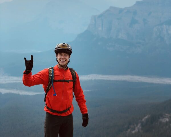 Man smiling in bike helmet and red jacket on mountain.