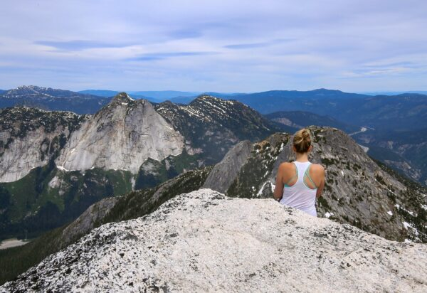 Woman sat on top of mountain looking at view.