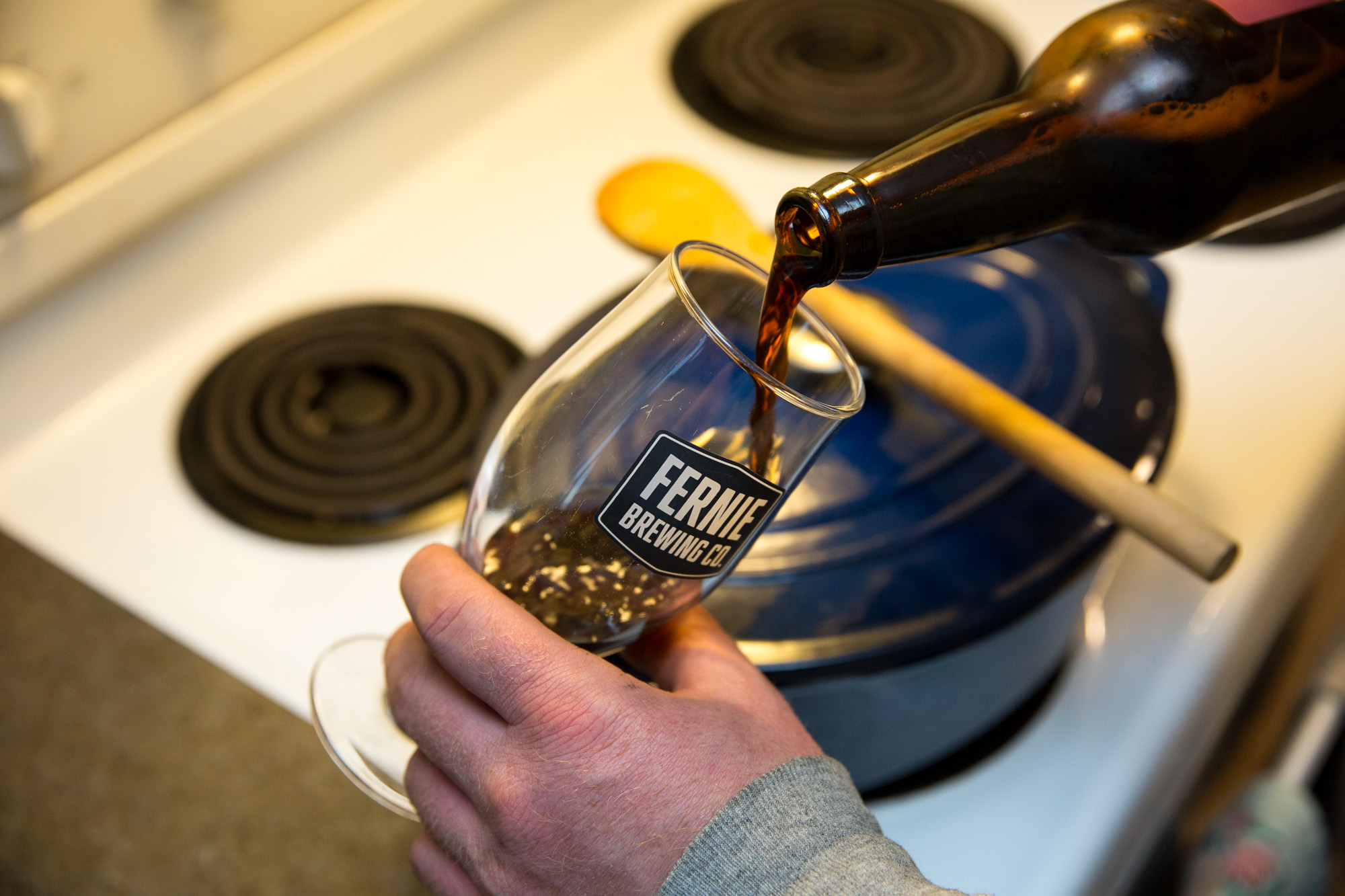 Beer being poured into a Fernie Brewing Co. glass next to a stove with a blue pot cooking on it.