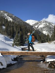 Freeskier Andrea Byrne walking over a bridge carrying skis in the backcountry.