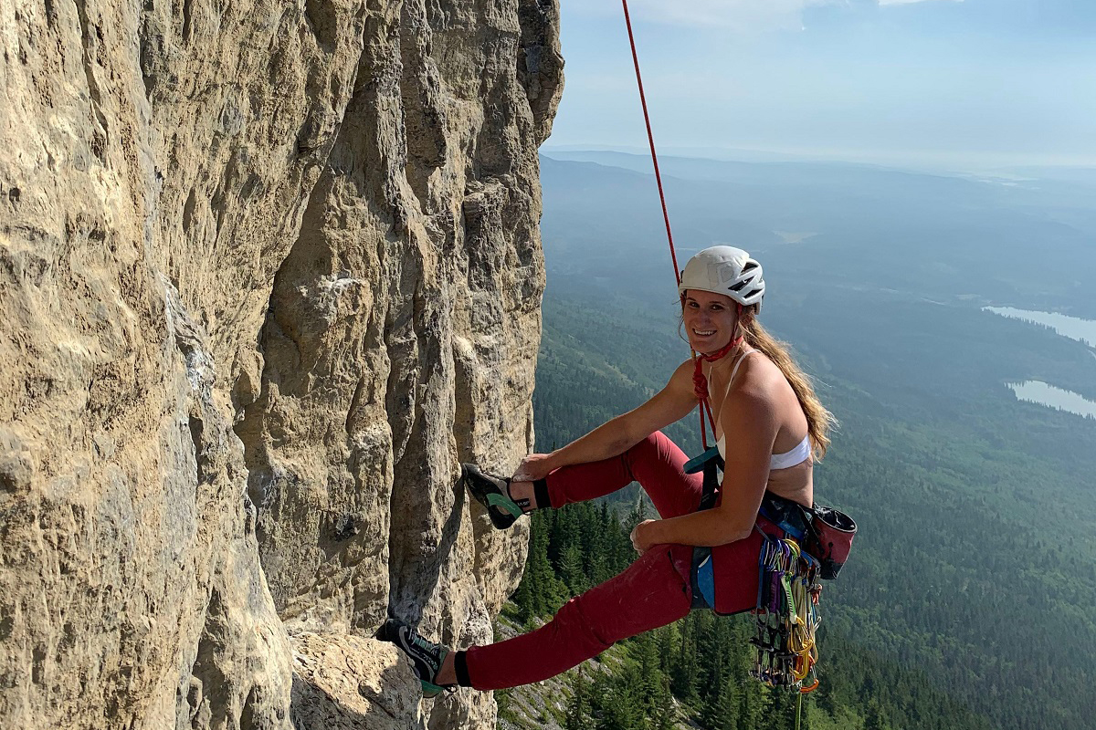 Jacqueline hanging during a rock climb.