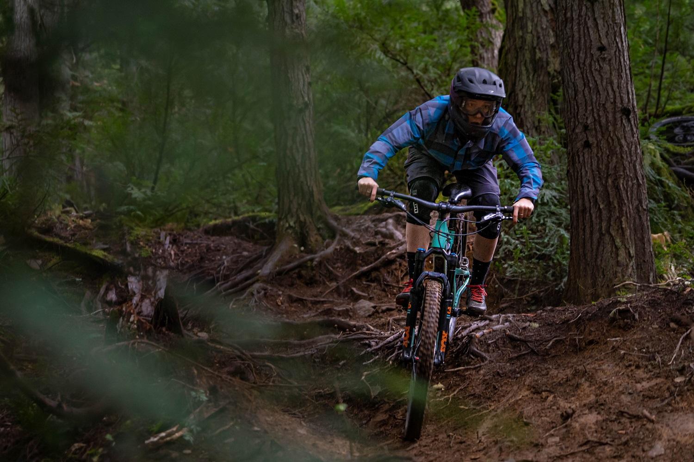 Micah mountain biking down a rooty path