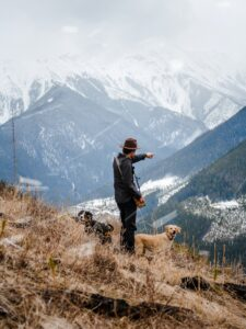 Man on a mountain pointing out into the wilderness