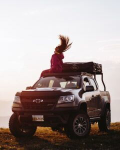 Girl swinging hair on top of a car